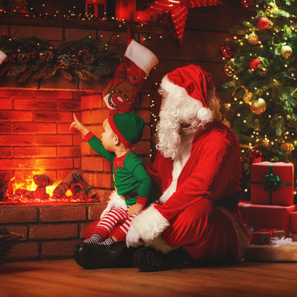Merry Christmas! Santa Claus and little elf near the fireplace